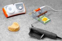 Dentist orthopedist tools, workplace of dental orthopedist, scalpel, milling cutter, form, tooth matrix, denture laboratory.  Stock Photography