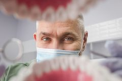 Dentist over open patient`s mouth looking in teeth. Oral care. I Royalty Free Stock Photos