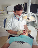 Dentist and patient. A dentist cleaning a patients teeth Stock Images