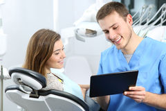 Dentist and patient commenting treatments in a tablet Stock Photo