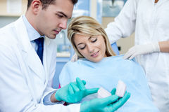 Dentist with patient and dental mold. Dentist explaining the details of dental mold to his patient stock image