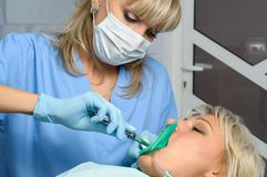 Dentist with patient, installation of rubber dam Royalty Free Stock Image