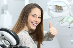 Dentist patient satisfied after treatment. Patient with perfect white teeth and smile satisfied after dental treatment in a dentist office with medical equipment Stock Image
