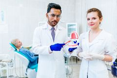 Two Dentist showing jaw model in clinic. Dentist with patient showing jaw model in clinic Royalty Free Stock Photo