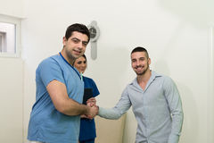 Dentist And Patient Smiling And Hand Shaking Stock Image