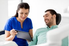 Dentist and patient with tablet pc at clinic. Medicine, dentistry and healthcare concept - female dentist showing tablet pc computer to male patient at dental Royalty Free Stock Photos