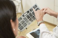 Dentist Pointing Towards A Cavity In Xray Report Stock Photo
