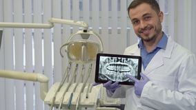 Dentist points his finger on the x-ray. Handsome brunette dentist pointing his forefinger on the x-ray. Attractive caucasian doctor looking at the tablet screen Stock Photos