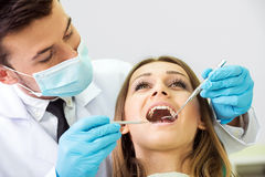 Dentist. Portrait of a dentist who treats teeth of young women patient Stock Image