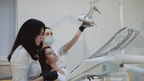 Dentist praparing for treatment and consulting girl. 4K. Dentist praparing for treatment and consulting girl in chair. 4K stock video footage