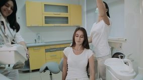 Dentist praparing for treatment female patient and consulting. 4K.  stock video footage