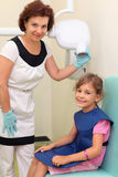 Dentist prepares girl to jaw x-ray image Royalty Free Stock Images