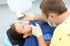 Dentist prepares to make x-ray image for girl Stock Photography