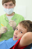 Dentist prepares to treat teeth of boy Stock Image