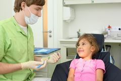 Dentist prepares to treat teeth of girl Stock Photos