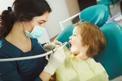 Dentist preparing drill tooth to child, little patient obediently opened his mouth, sitting on chair. stock photography