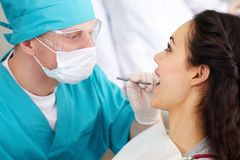 Dentist in protective glasses Stock Photos