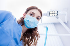 Dentist in protective mask holding dental supply in dental clinic Royalty Free Stock Photo