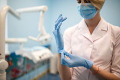 The dentist puts gloves before the operation. Close-up Royalty Free Stock Photo