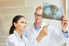 Dentist and radiologist holding x-ray image. And making diagnostic for patient royalty free stock images
