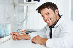 Dentist with x-ray image in dental practice. Dentist pointing with his finger at x-ray image in dental practice stock images