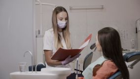Dentist reads a patient the prices for treatment teeth. Young woman sits on dentist chair in stomatology clinic and listens the dentist. The doctor holds a stock video footage