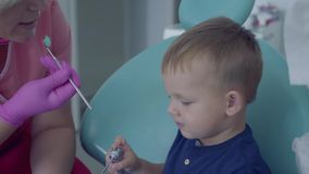 Dentist ready to checking tooths of little carefree boy sitting in the chair in the dental office. Female professional. Doctor stomatologist at work. Dental stock video footage