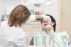 At the dentist's. Female dentist examining a patient Stock Image