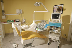 Dentist's chair. In a yellow studio Stock Image