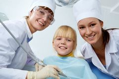 In dentist's office. Group of dentist, assistant and little girl looking at camera Royalty Free Stock Image