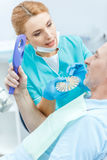 Dentist with samples comparing teeth of mature patient looking at mirror Royalty Free Stock Photography