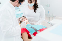 Dentist seeing pregnant woman in his office royalty free stock photos
