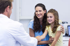 Dentist shaking hand with daughter after dental examination Royalty Free Stock Photo
