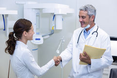 Dentist shaking hand with female patient Royalty Free Stock Photography
