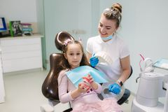 Dentist show to little girl how to wash teeth royalty free stock images