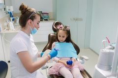 Dentist show to little girl how to wash teeth royalty free stock photography