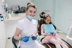 Dentist show to little girl how to wash teeth stock image