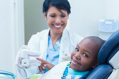 Dentist showing boy prosthesis teeth Royalty Free Stock Images