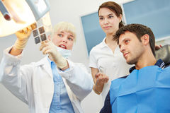 Dentist showing caries on x-ray image. Female dentist showing caries on x-ray image to a patient before treatment Royalty Free Stock Photos