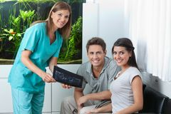 Dentist Showing Dental X-Ray To Couple Royalty Free Stock Images