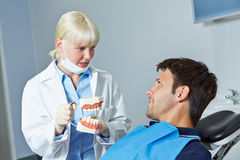 Dentist showing denture to patient Royalty Free Stock Images