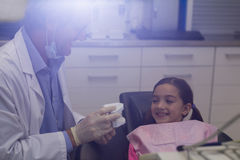 Dentist showing model teeth to patient Stock Photos
