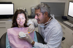 Dentist showing mouth model to female patient Royalty Free Stock Photos