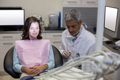 Dentist showing mouth model to female patient Stock Photo