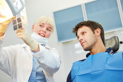 Dentist showing patient caries on x-ray image Royalty Free Stock Image