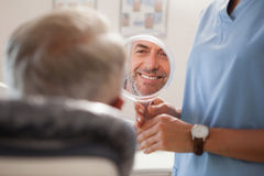 Dentist showing patient his new smile in the mirror Royalty Free Stock Image