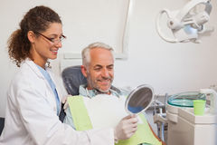 Dentist showing patient his new smile in the mirror Royalty Free Stock Photo