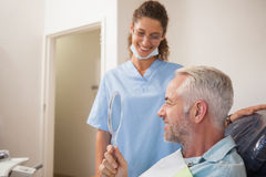 Dentist showing patient his new smile in the mirror Royalty Free Stock Photography