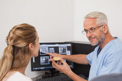 Dentist showing patient model of teeth and xrays Royalty Free Stock Photography