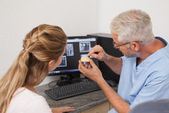 Dentist showing patient model of teeth and xrays Stock Photos